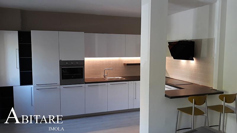 cucina bianca con piano colazione snack arredare casa interior design imola bologna provincia illuminazione led cappa nera induzione