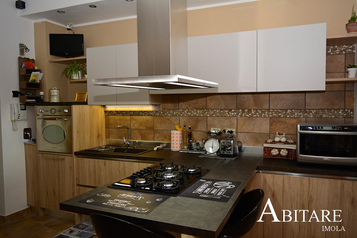 cucina oikos agora con penisola cappa centro stanza falmec piano cottura vetro arredamento imola bologna